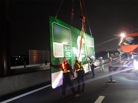 交通安全施設工事  新名神高速道路 城陽ジャンクション標識工事  高速道路の門型柱への案内標識板吊上げ状況写真(その1)