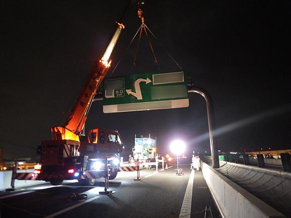 交通安全施設工事  新名神高速道路 城陽ジャンクション標識工事 高速道路の門型柱への案内標識板吊上げ状況写真(その2)