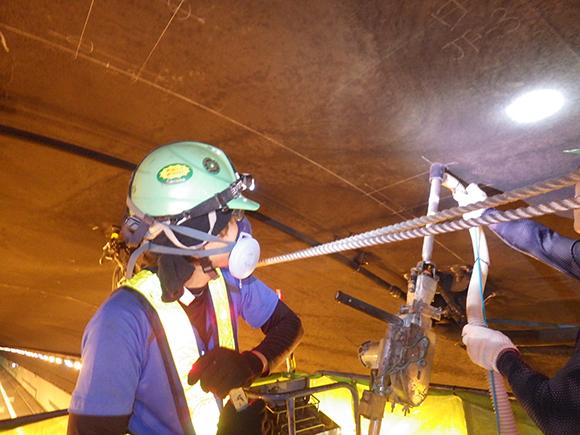 あと施工アンカー工事 交通安全施設工  関西東部地区 機械・電気施設保全工事 あと施工アンカー設置用の削孔状況写真、粉塵が出ないように吸塵式ビットを採用