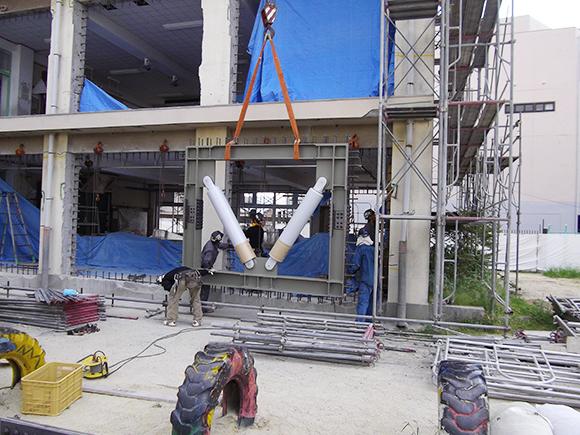 耐震補強工事(建築耐震) 市立藤井寺小学校1・13号棟地震補強工事 枠付き免震ダンパー設置前、ラフターによる吊上げ状況写真(その2)